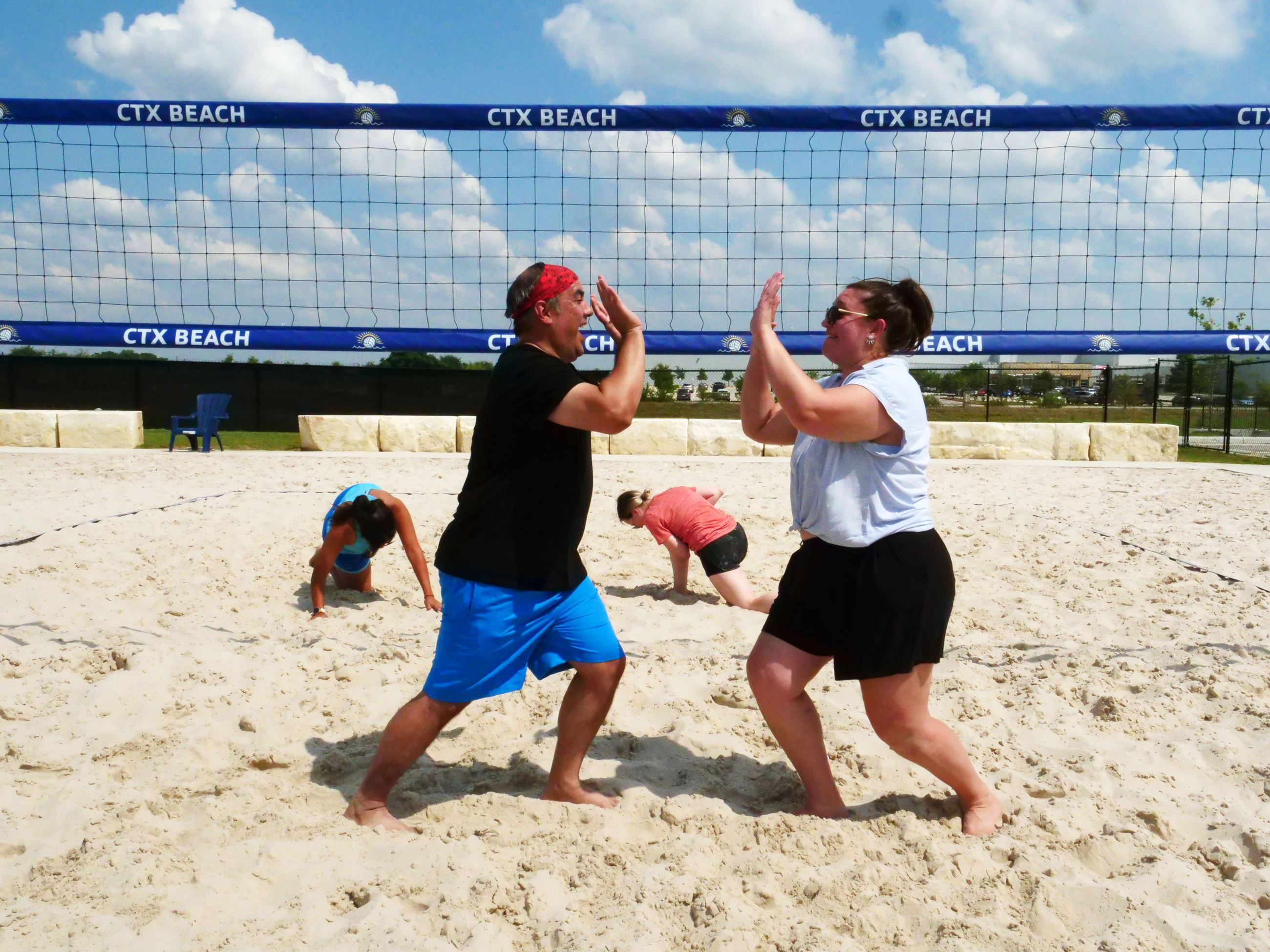 Two players high five after a score in the sand volleyball courts