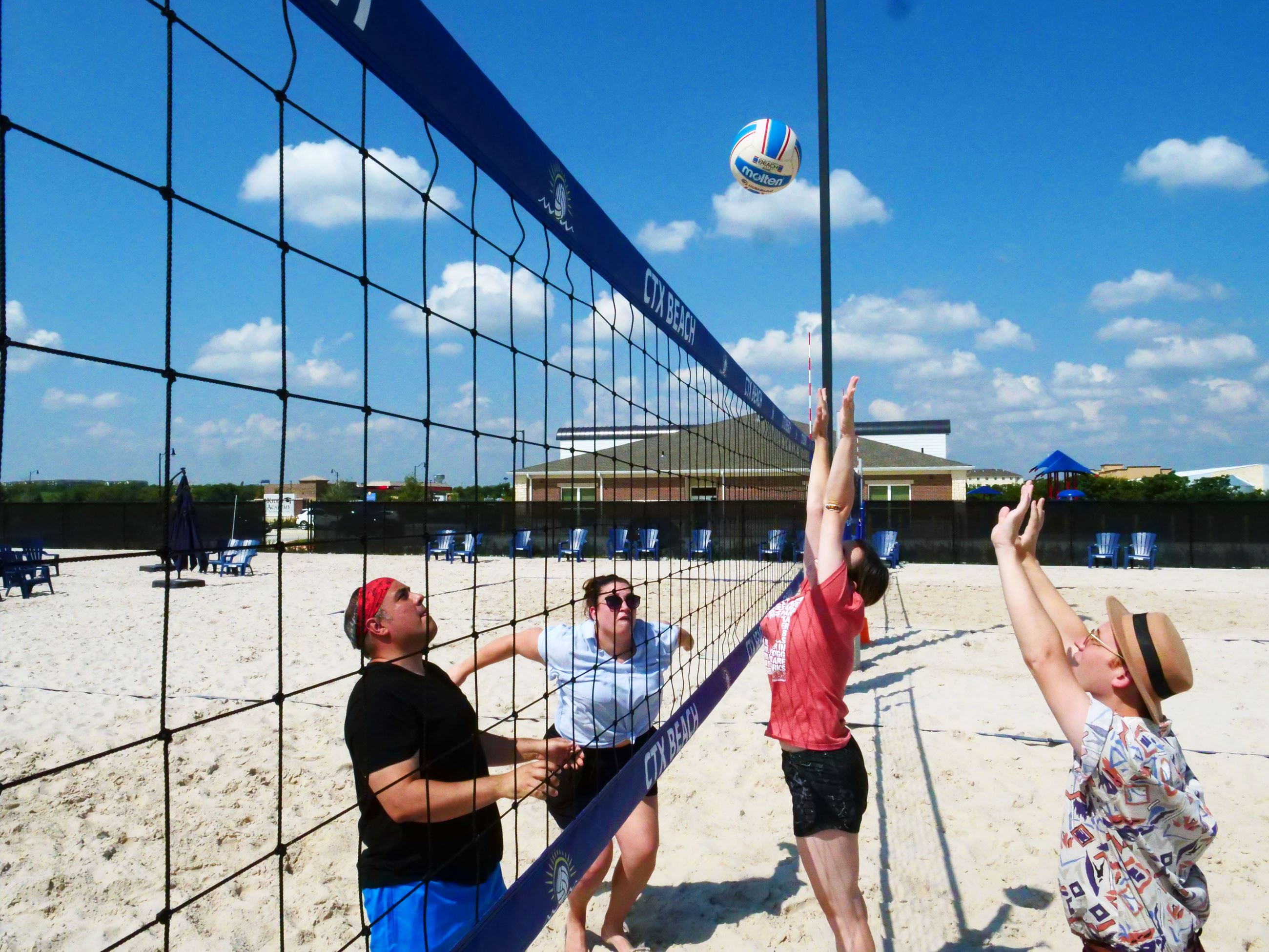4 player jump for the ball at the net in sand volleyball courts