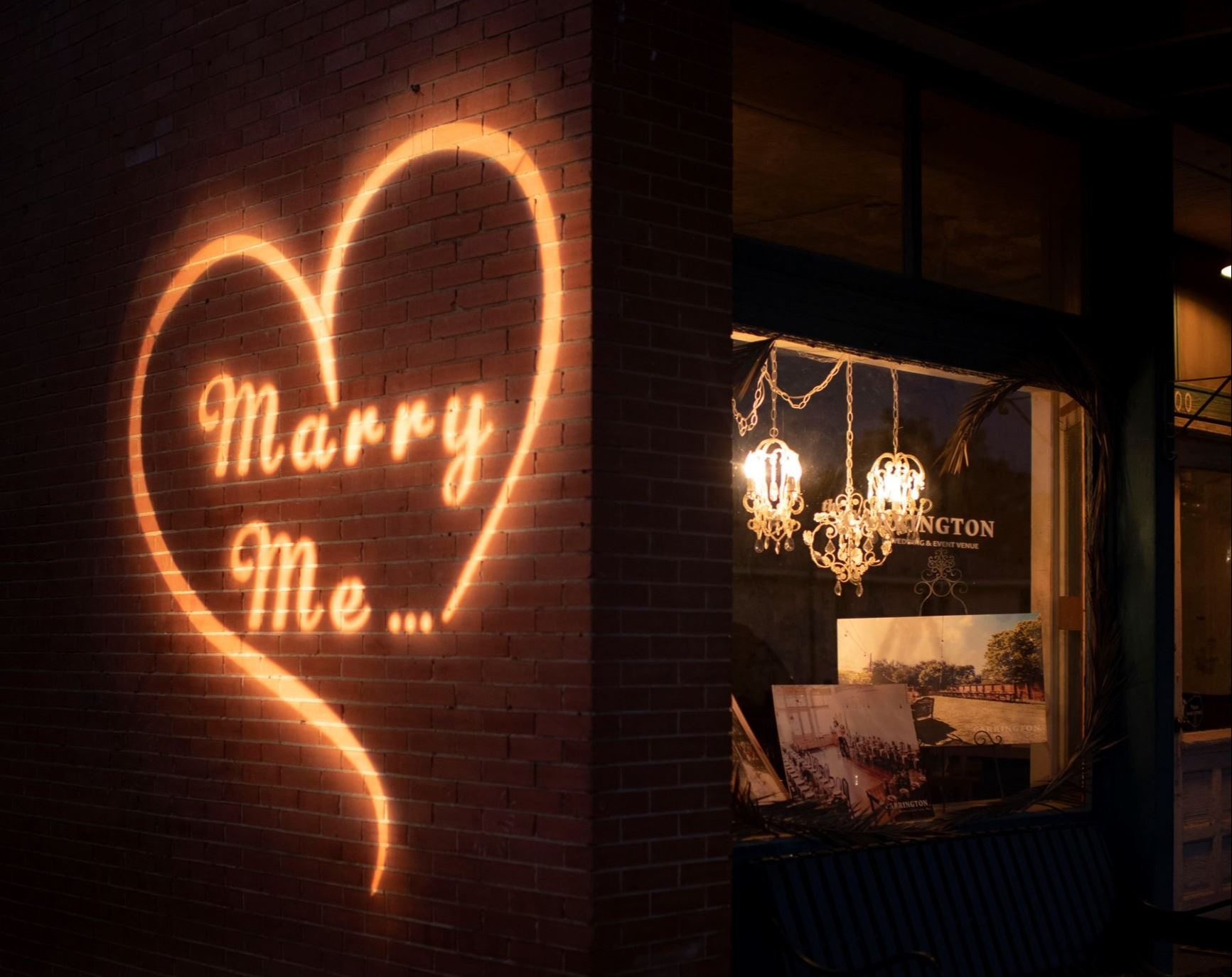 inscription Marry Me inside of a heart projected on the brick outside of the Carrington wedding venue at
