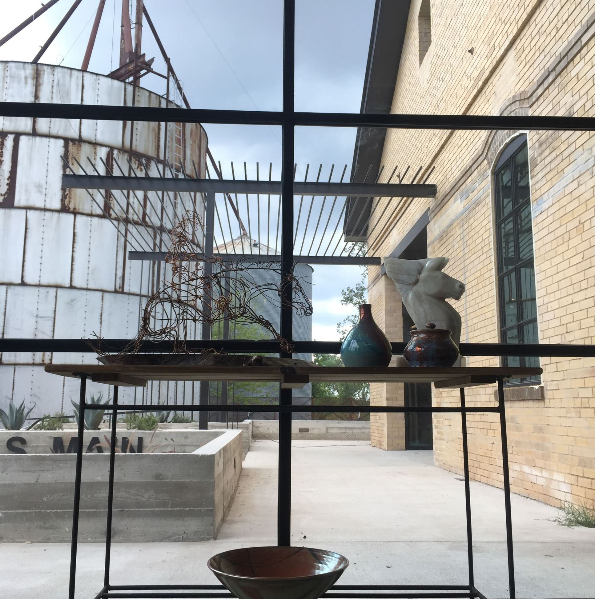 Art sculptures at Assemblage with background view of old silos in the window