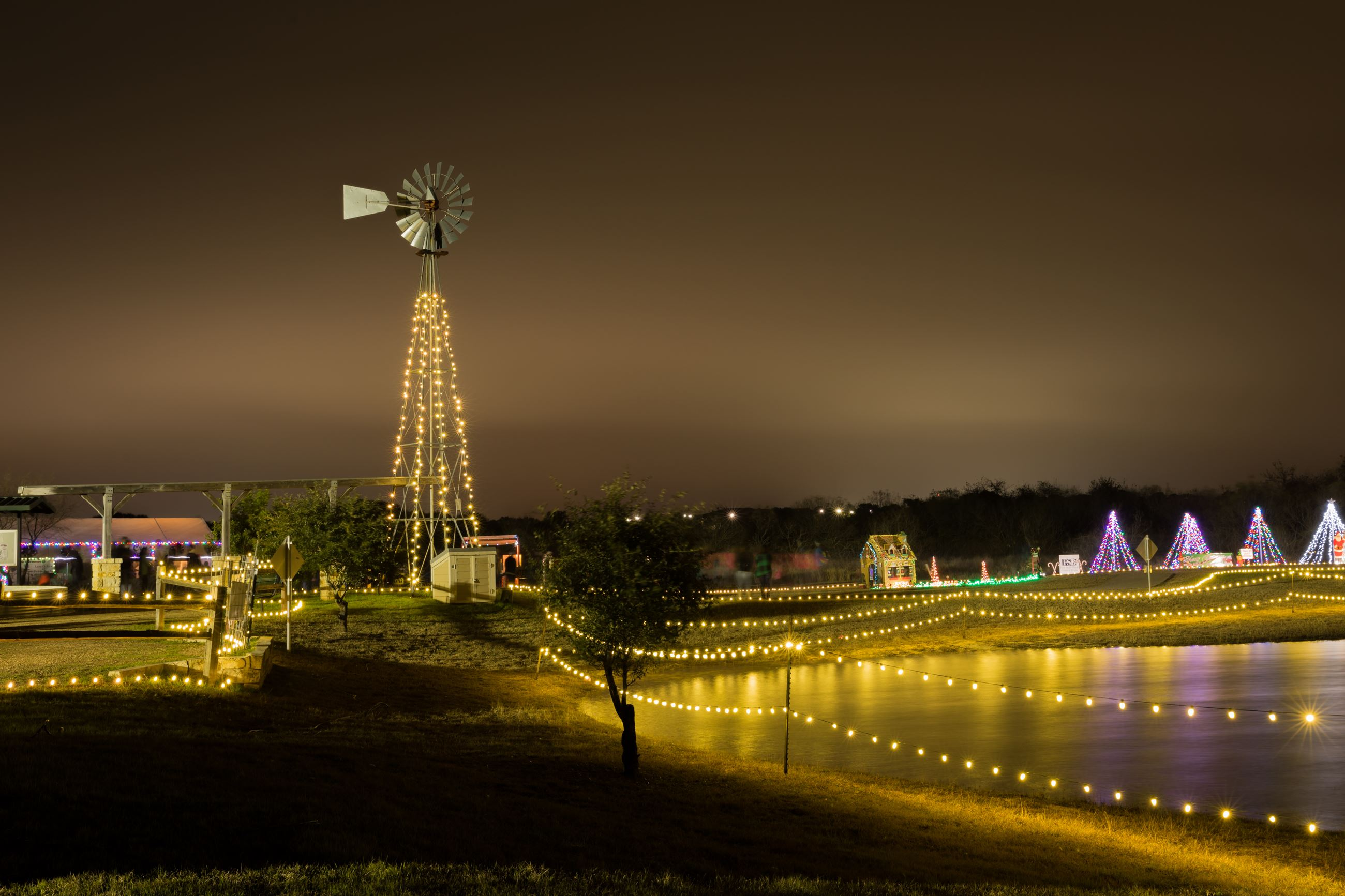View of Stagecoach Park pond and windmill at night during Trail of Lights