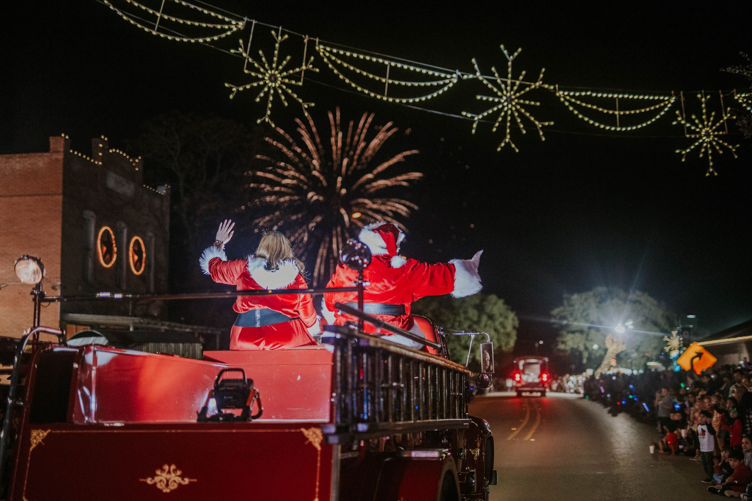 Santa and Mrs. Claus riding on a vintage fire truck during the Budafest parade with fireworks behind