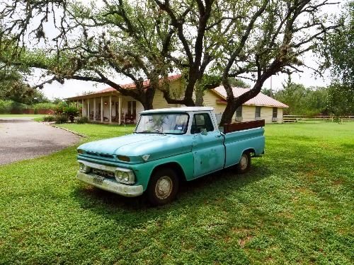 Teal vintage truck in the grass in front of Ruby Ranch main house